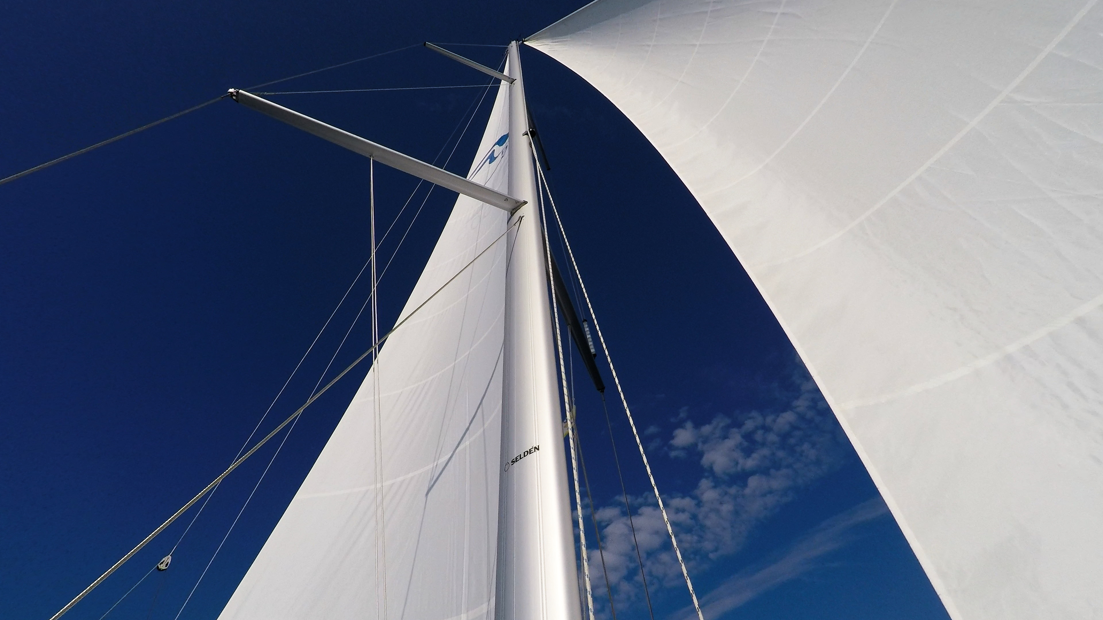 Segelyacht blauer Himmel weiße Segel Mast Takelwerk Genua Großsegel Segelboot Segeln